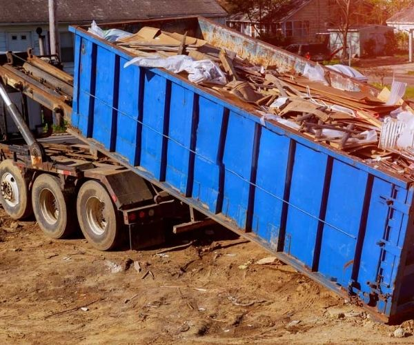 large blue skip bin with wood and concrete waste types